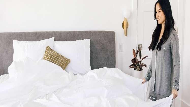 lady fluffing sheets on a leesa mattress over pillows